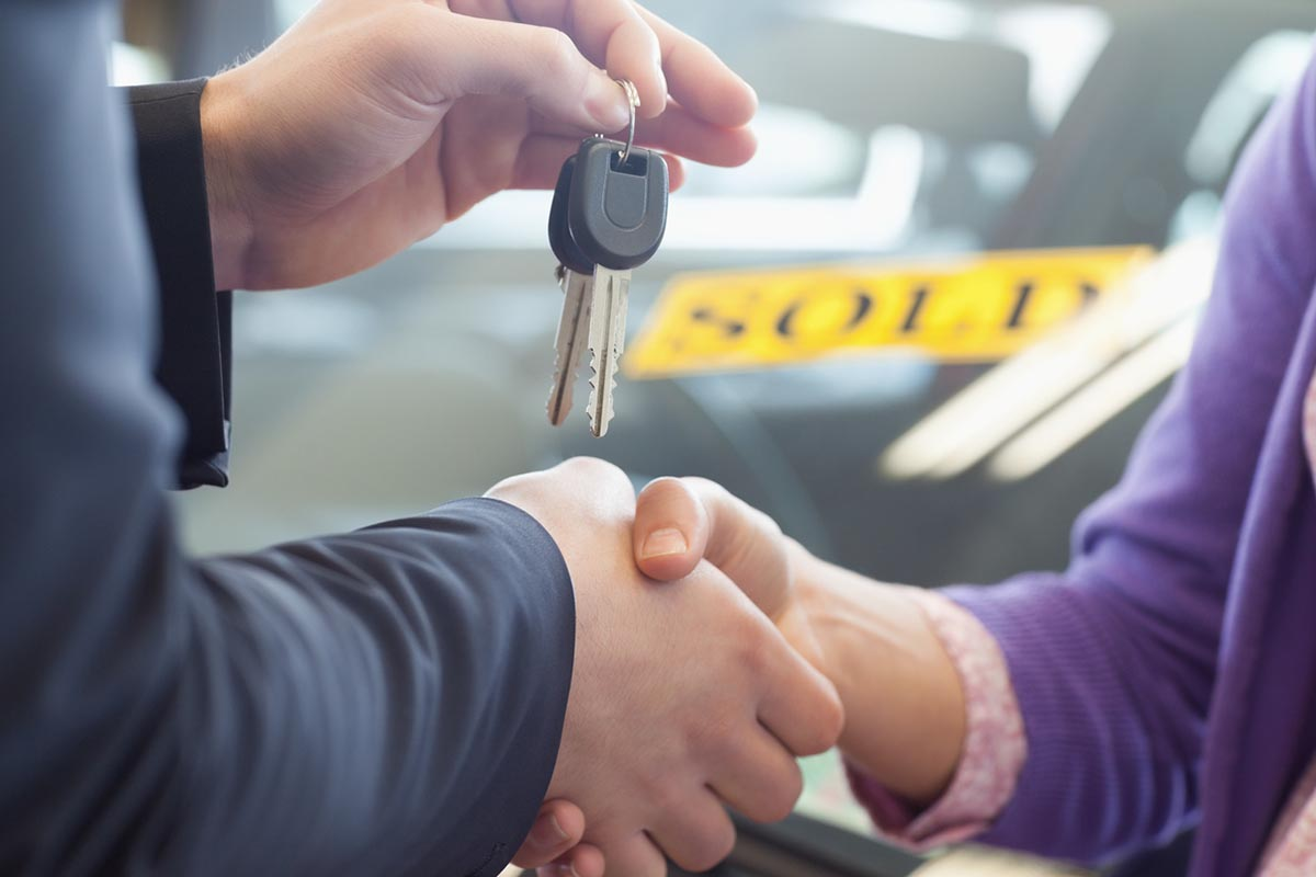 man giving car keys to new owner